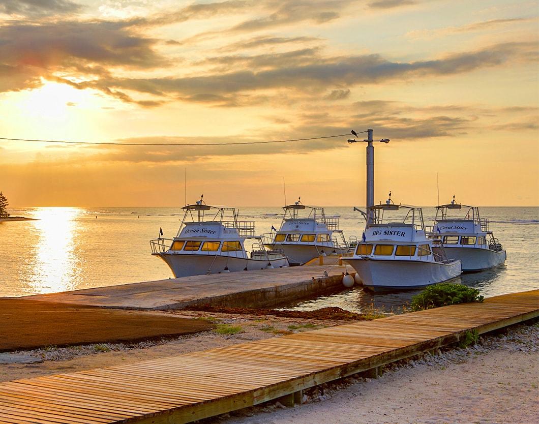 cayman brac four boats docked sunset 1060x834min
